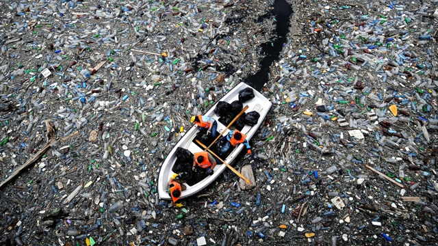 A boat sails through a garbage pat