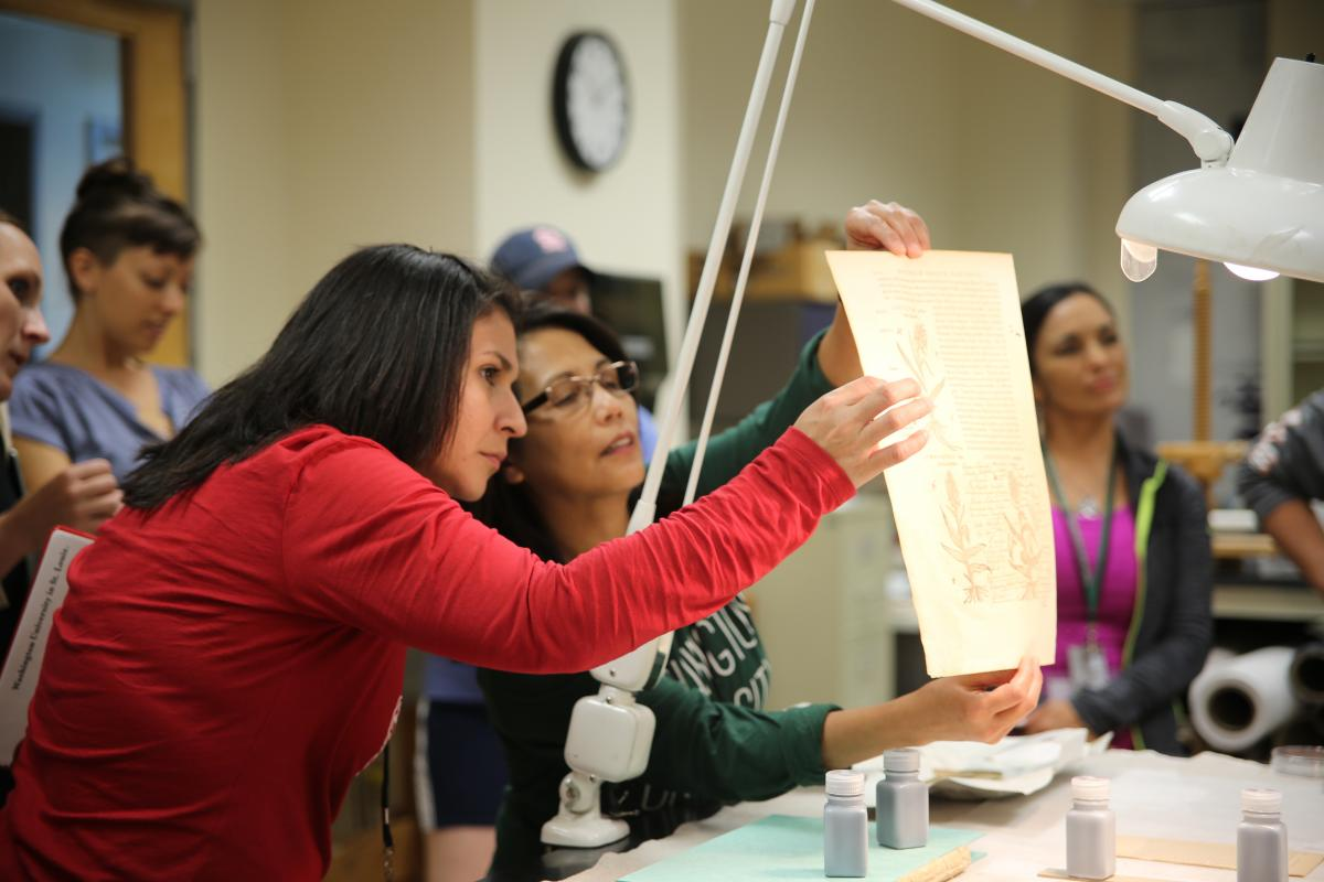 Gloria Garza and Nellie Kvapil (left to right) examine a document while learning about book binding during a tour of the plant and rare book library at the Missouri Botanical Garden's Monsanto Research Building.