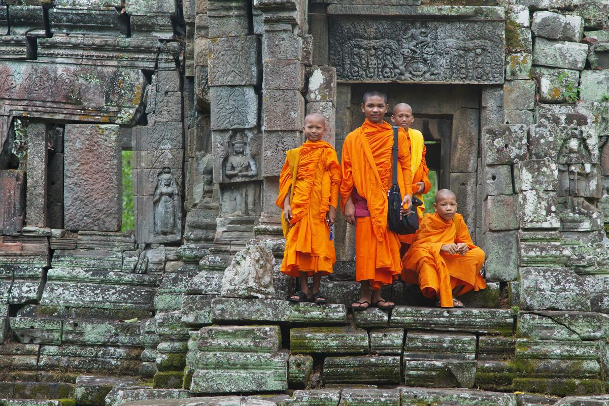 Young buddhist monks stand in front of their temple