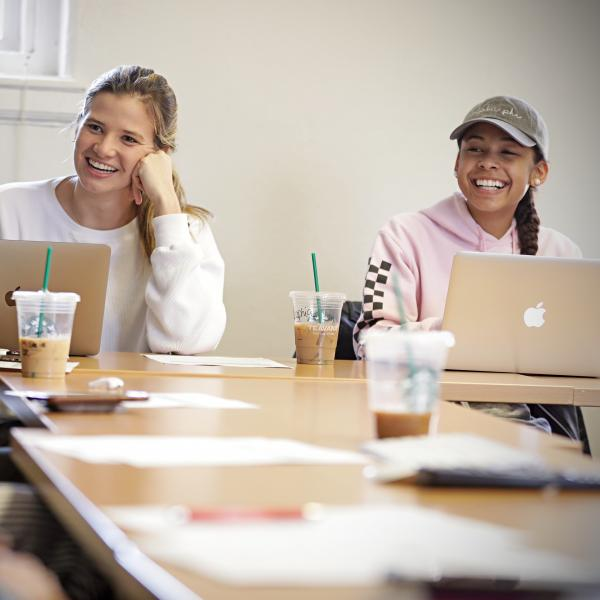 Two students laughing in a classroom.