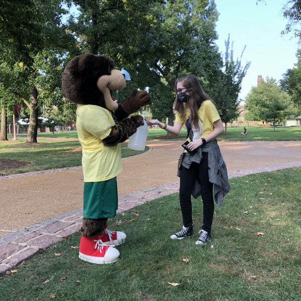 The WashU bear gives hand sanitizer to a Student Health Ambassador.