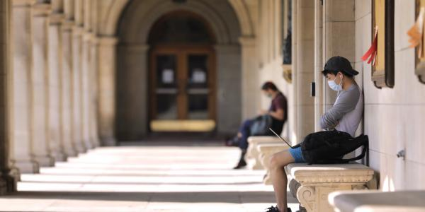 Student sits in walkway on campus while on his computer.