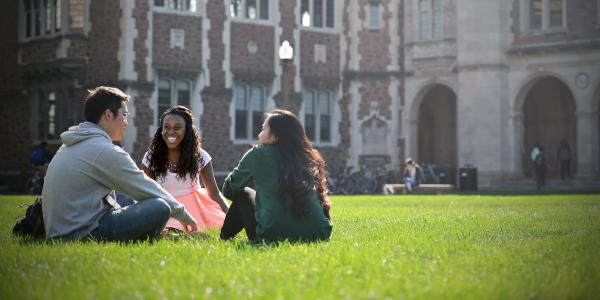 Three students sit on the grass in the JWB quad.
