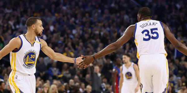 Kevin Durant and Stephen Curry high five during a game