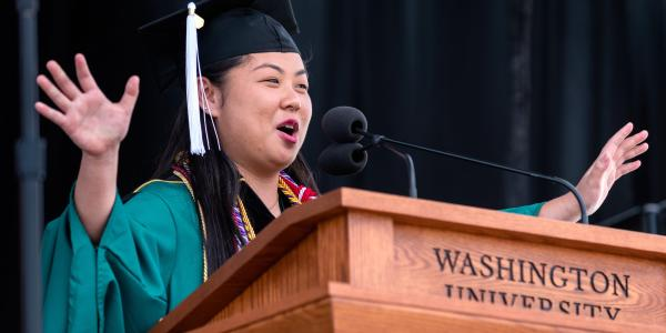 A female student stands at a podium and addresses the graduates.
