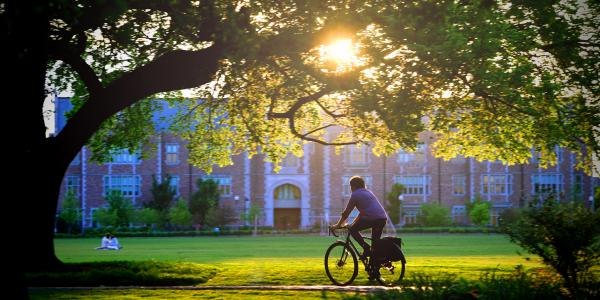 student riding bike on campus